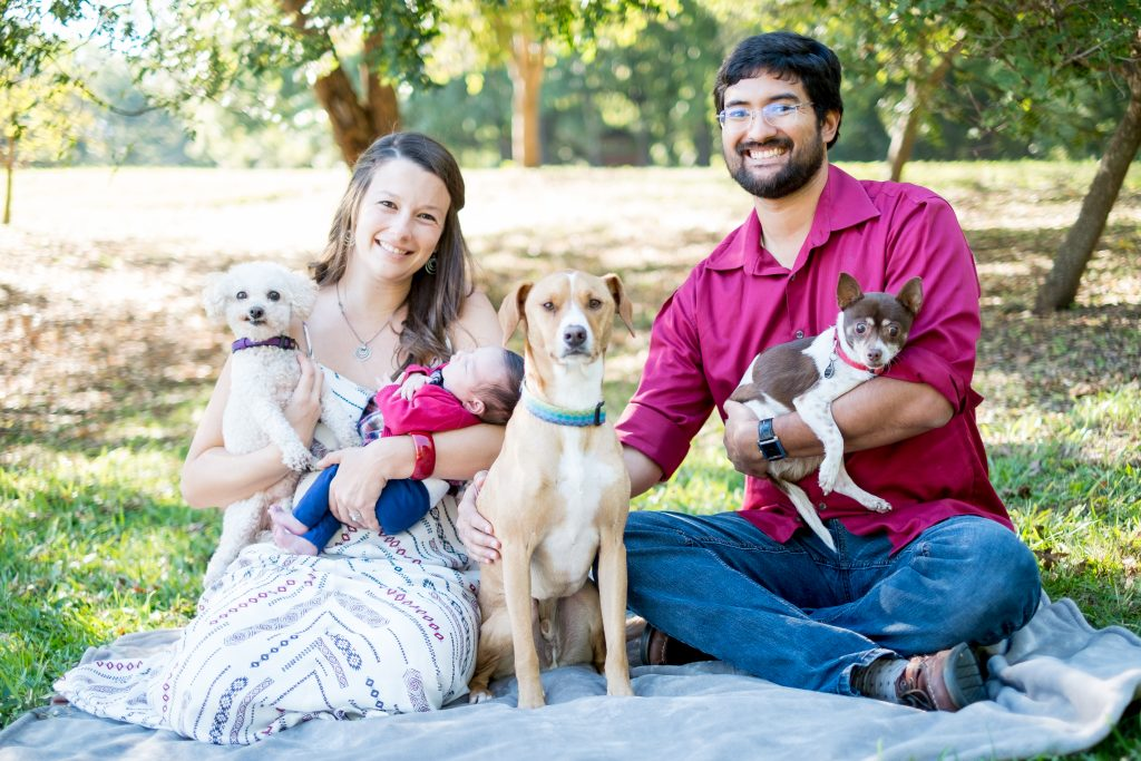 A family photo of a couple with their pets, at a park in Raleigh, NC.
