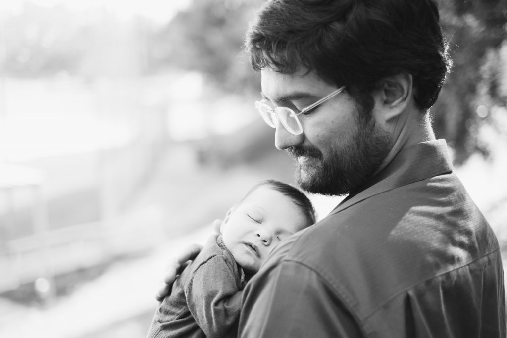 A black and white family photo of a father and his newborn.