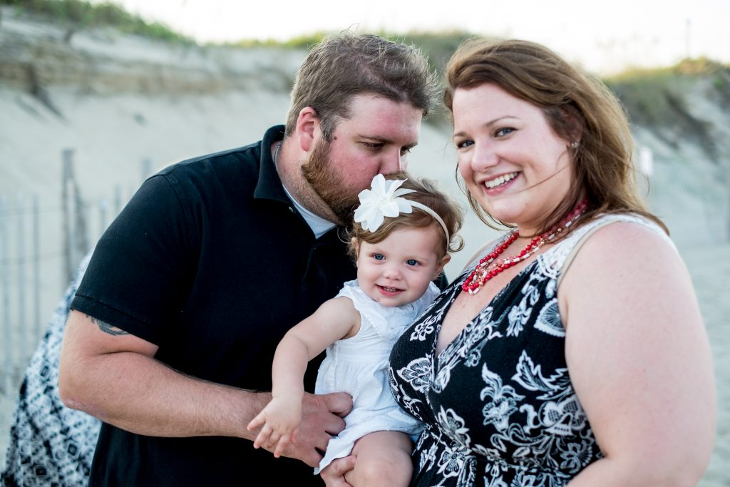 A family photo of a husband and wife holding their newborn, at Cape Hatteras, NC.