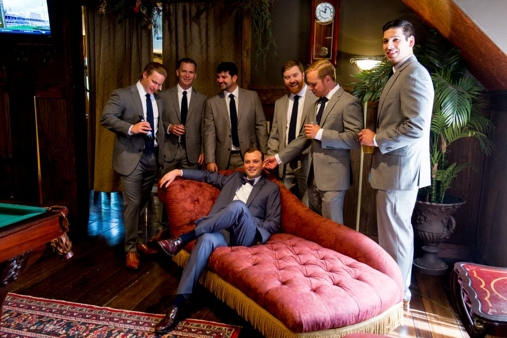 A groom, resting on a chaise lounge chair, surrounded by his groomsmen. Photo taken by Pait photography, at a wedding at Barclay Villa, in Angier, NC.