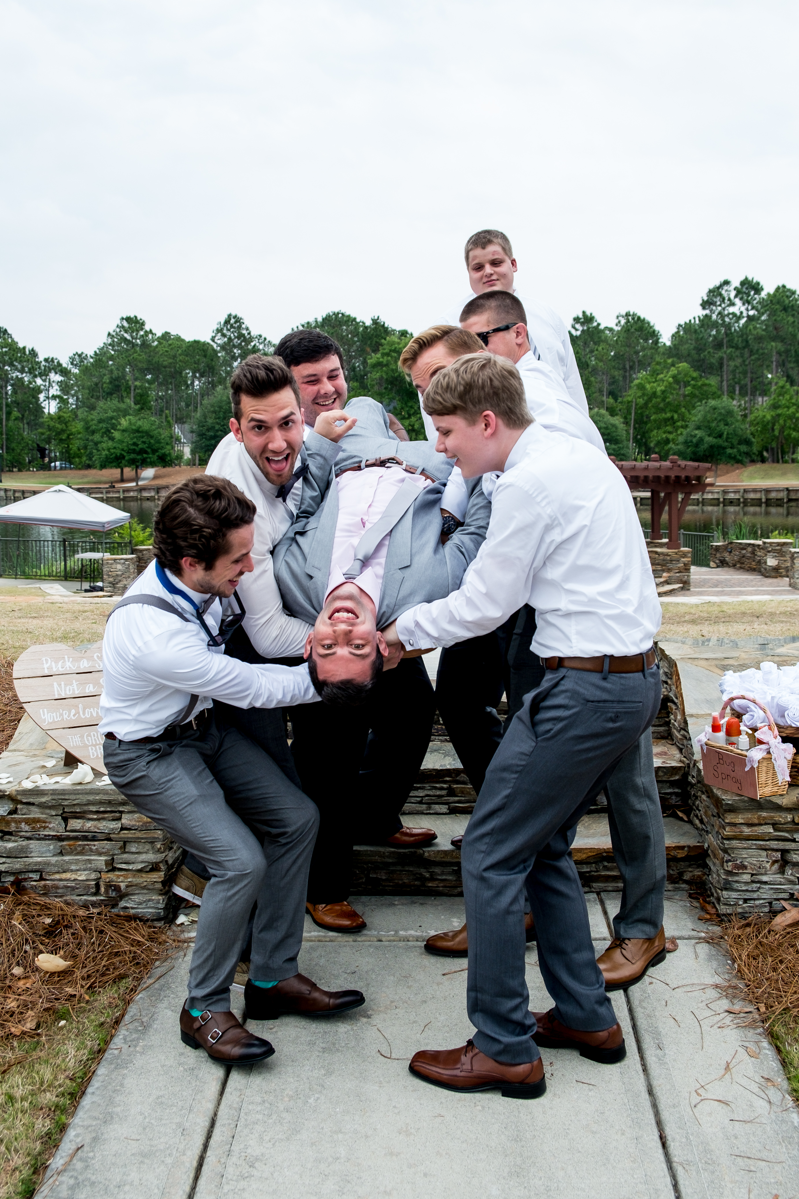 A groom on his back, being held by his groomsmen, before his wedding. Photo taken by Pait Photography, at a wedding at St. James Plantation, in St. James, NC.