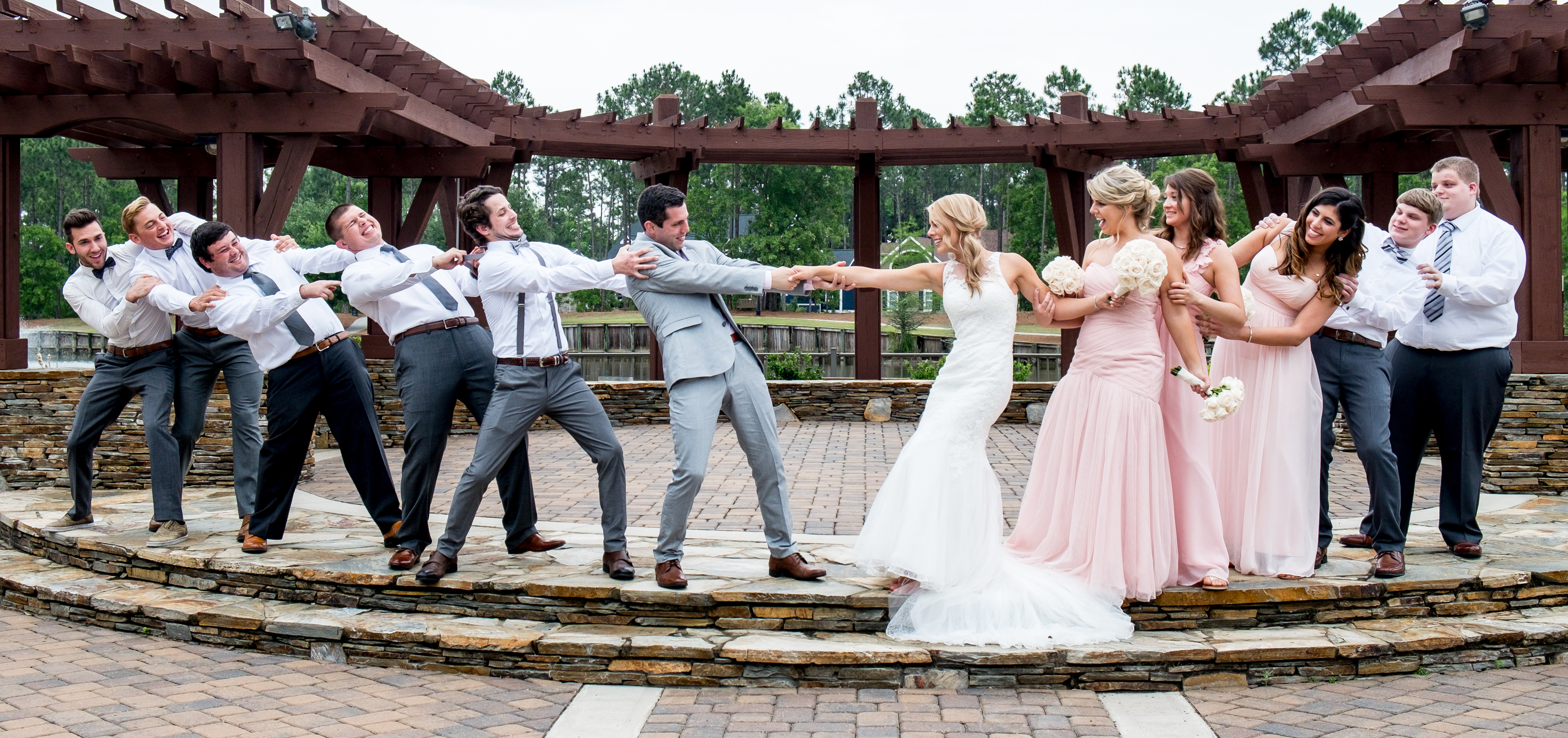 Bridesmaids and groomsmen playfully pretending to pull the bride and groom apart. Photo taken by Pait Photography, at a wedding at St. James Plantation, in St. James, NC.