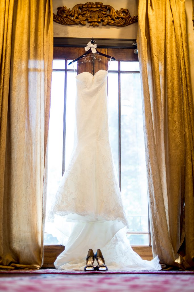 A wedding dress hanging in front of a window. Photo taken by Pait photography, at a wedding at Barclay Villa, in Angier, NC.