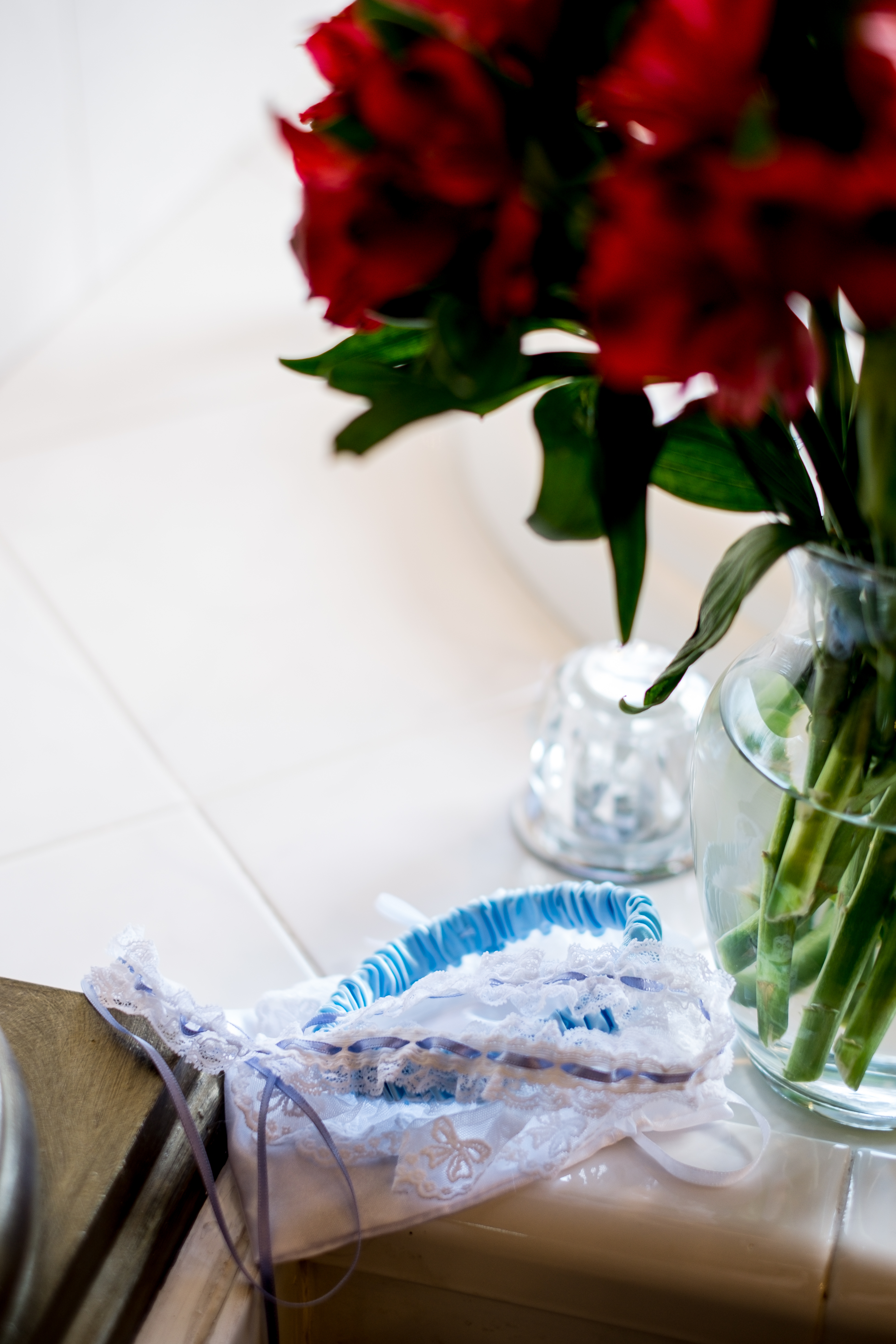 A garter and roses, sitting on a tile floor. Photo taken by Pait photography, at a wedding at Barclay Villa, in Angier, NC.