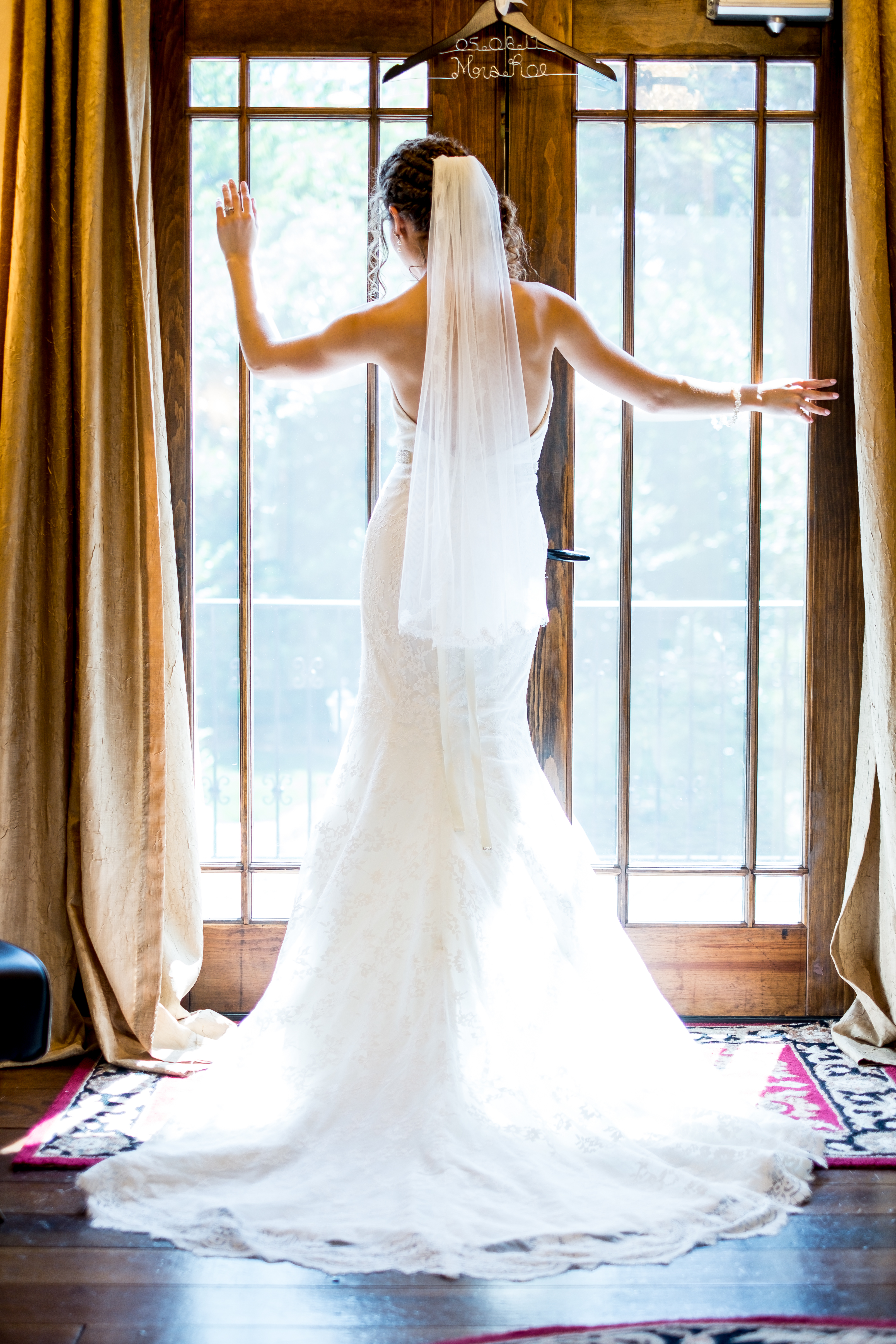 A bride standing in front of a window. Photo taken by Pait Photography, at a wedding at Barclay Villa, in Angier, NC.