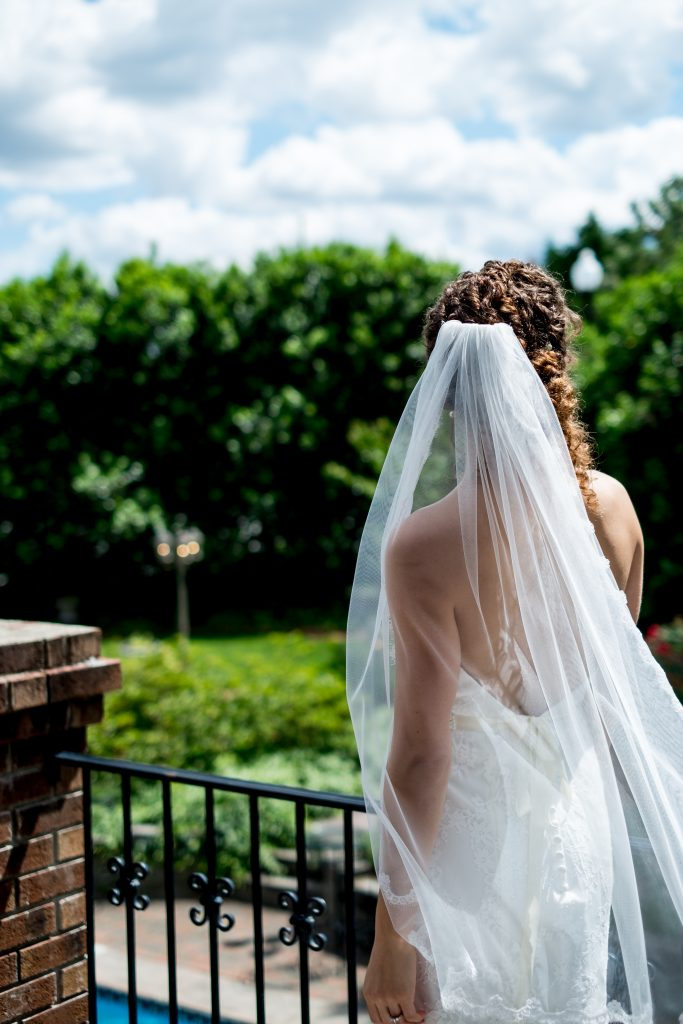 A bride looks out over a garden, from her balcony. Photo taken by Pait Photography, from a wedding at Barclay Villa, in Angier, NC.