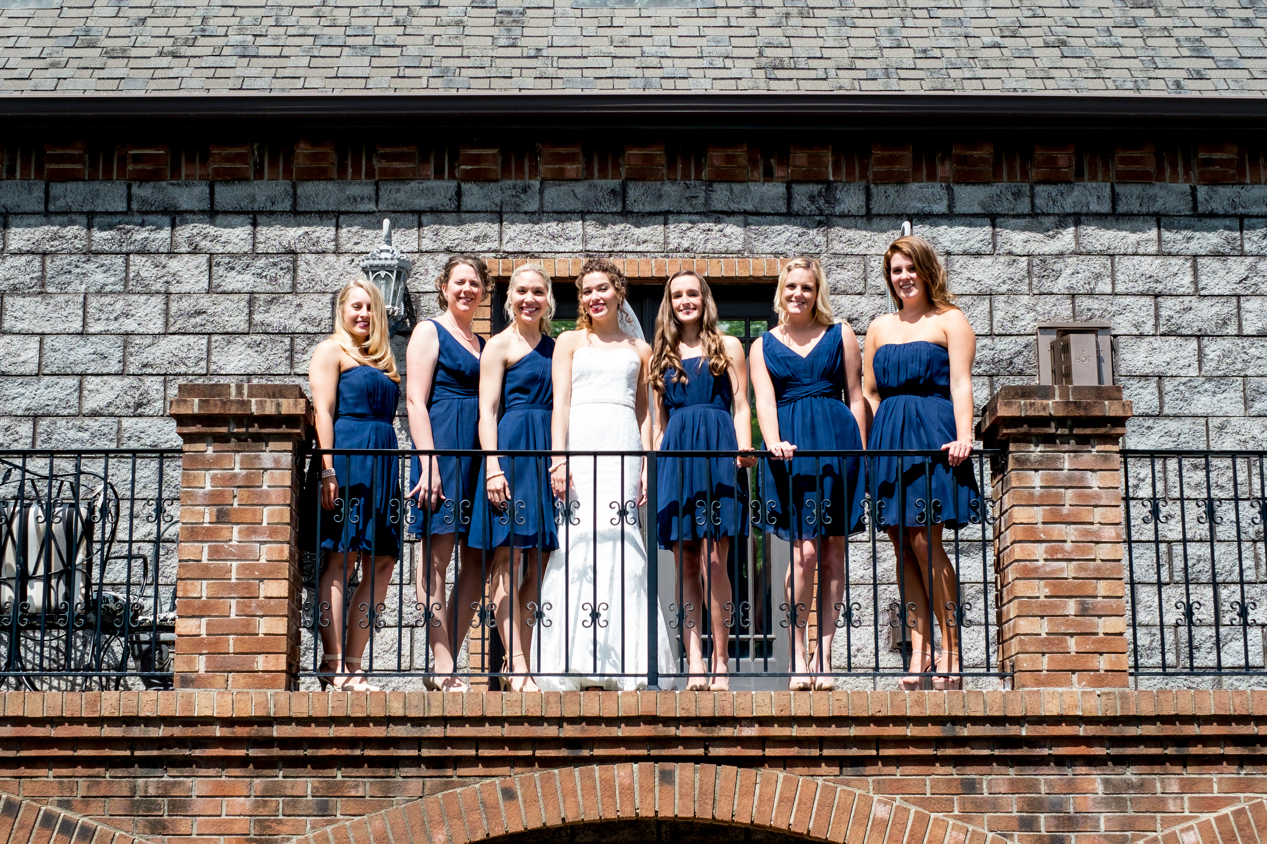 A bride, surrounded by her bridesmaids, standing on a balcony. Photo taken by Pait Photography, at a wedding at Barclay Villa, in Angier, NC.