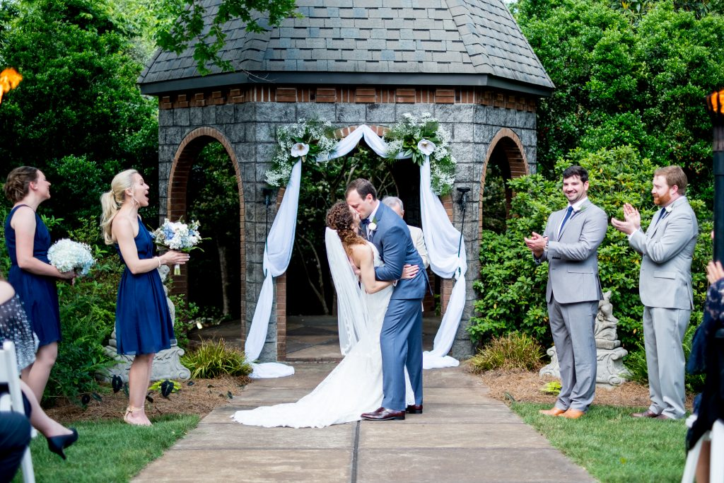 A bride and groom share their first kiss, in front of their guests. Photo taken by Pait photography, at a wedding at Barclay Villa, in Angier, NC.