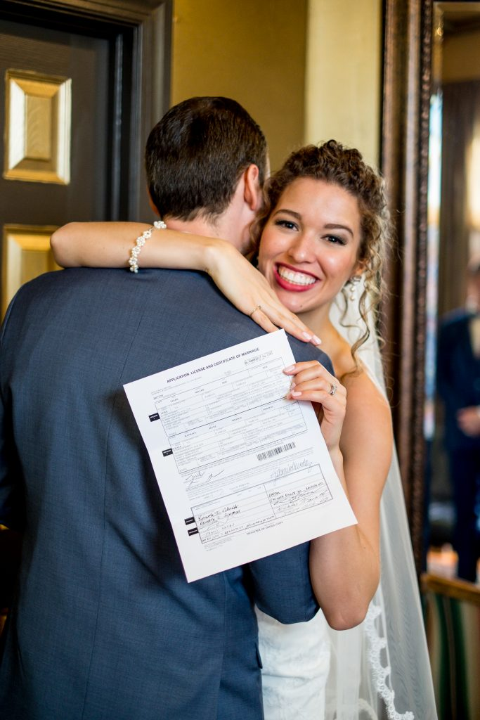 A bride shows off her marriage certificate, while holding her groom. Photo taken by Pait Photography, from a wedding at Barclay Villa, in Angier, NC.