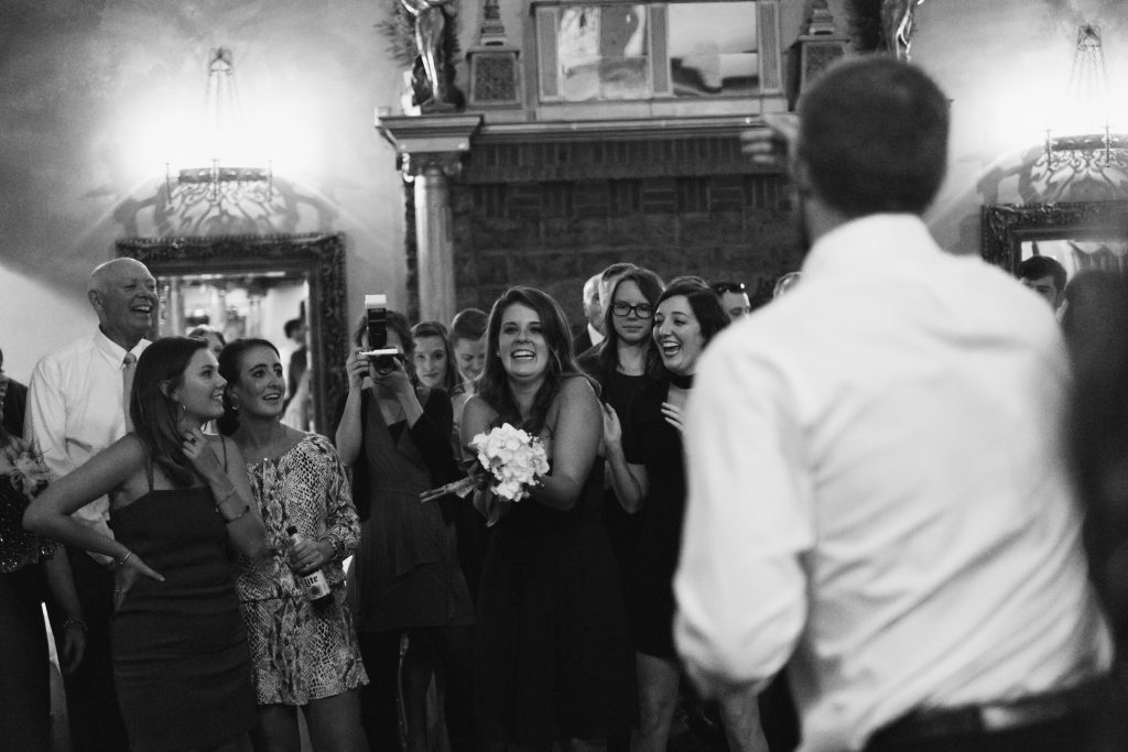 A black and white photograph of a bridesmaid catching the bouquet. Photo taken by Pait Photography, from a wedding at Barclay Villa, in Angier, NC.