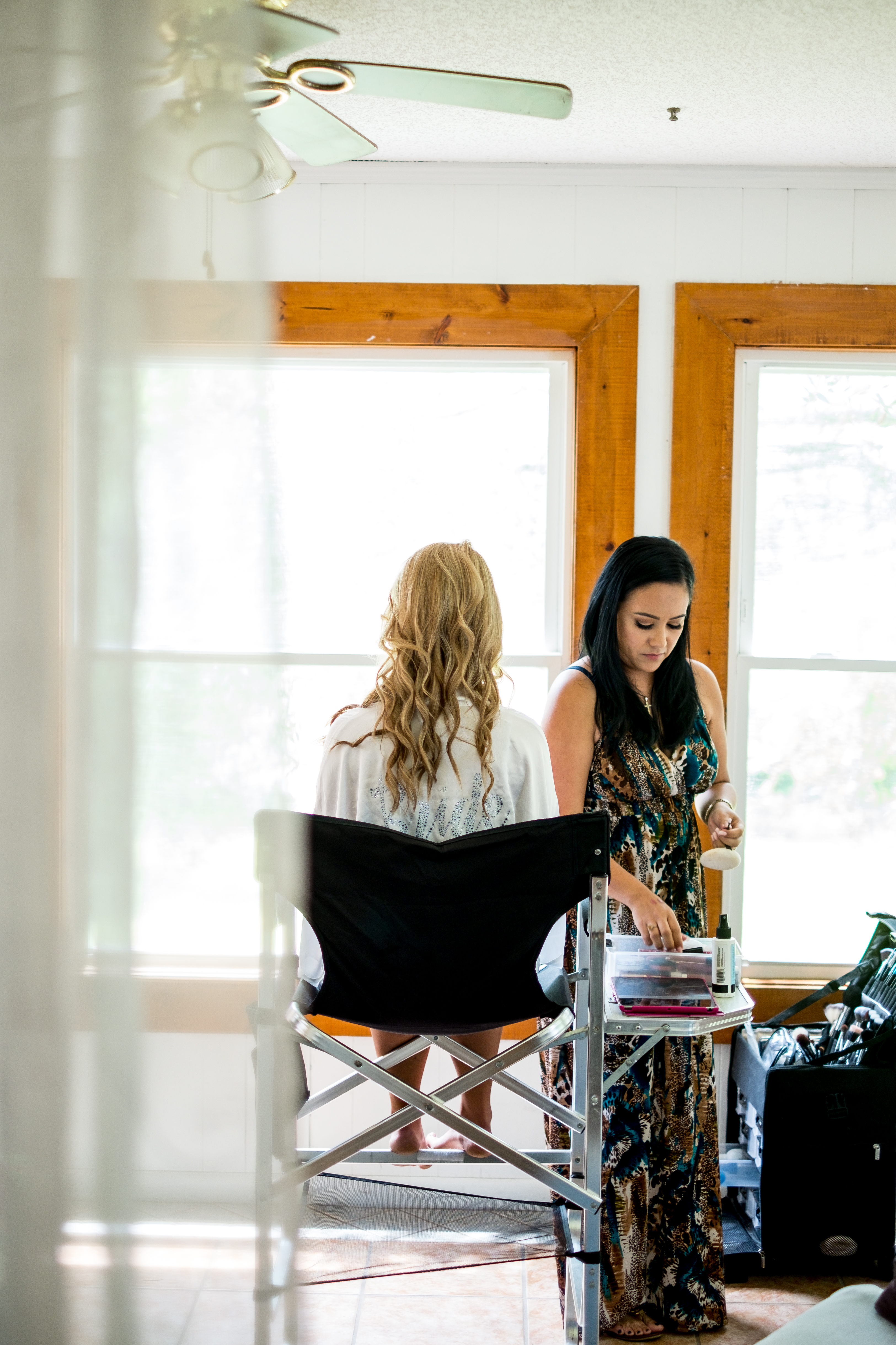 A photo of a bride sitting in her chair, as a makeup artist prepares her for her wedding day. Photo taken by Pait Photography, at a wedding at St. James Plantation, in St. James, NC.