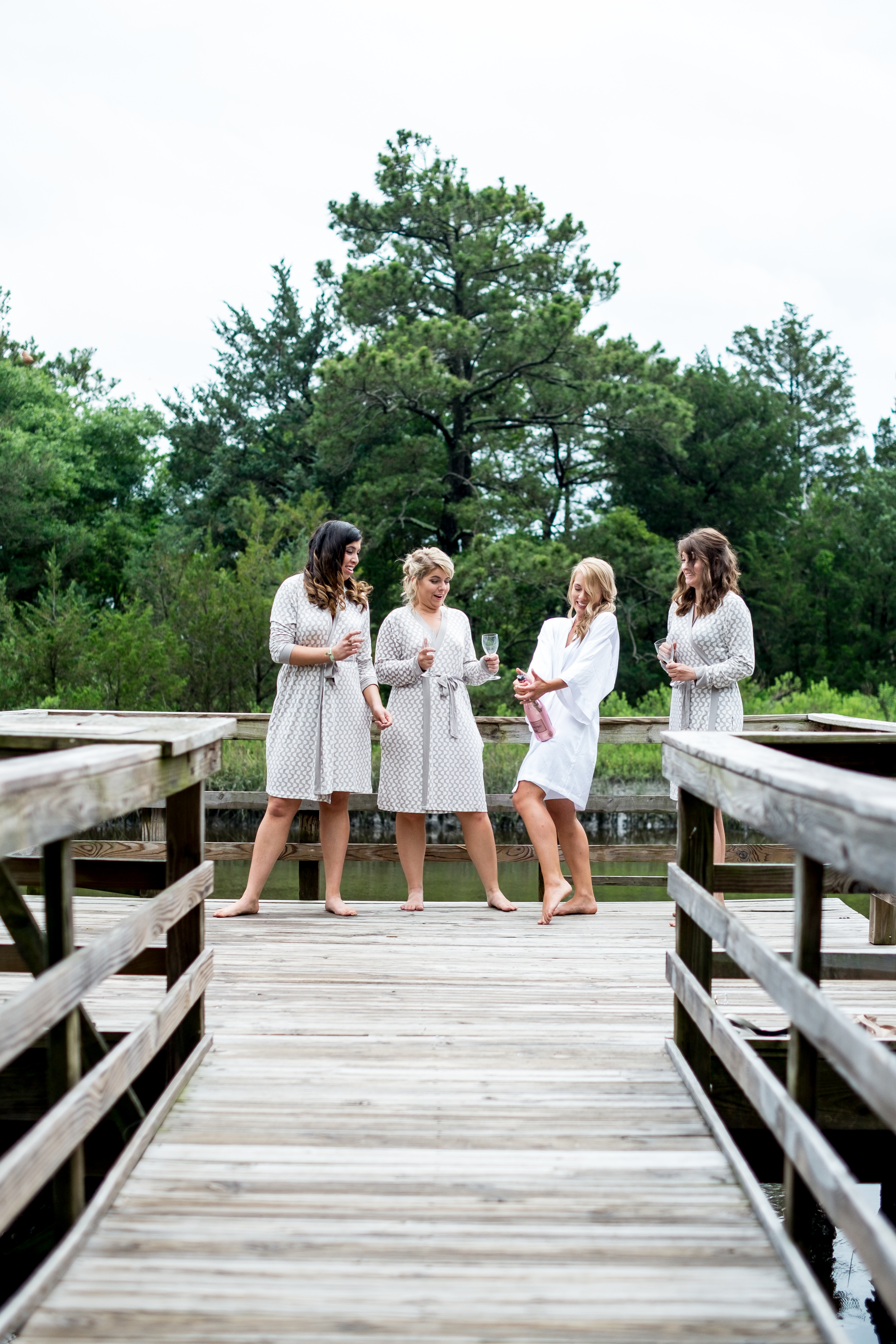 A bride and her bridesmaids stand at the end of a pier, on the intercoastal waterway, popping the cork on a bottle of champagne. Photo taken by Pait Photography, at a wedding at St. James Plantation, in St. James, NC.
