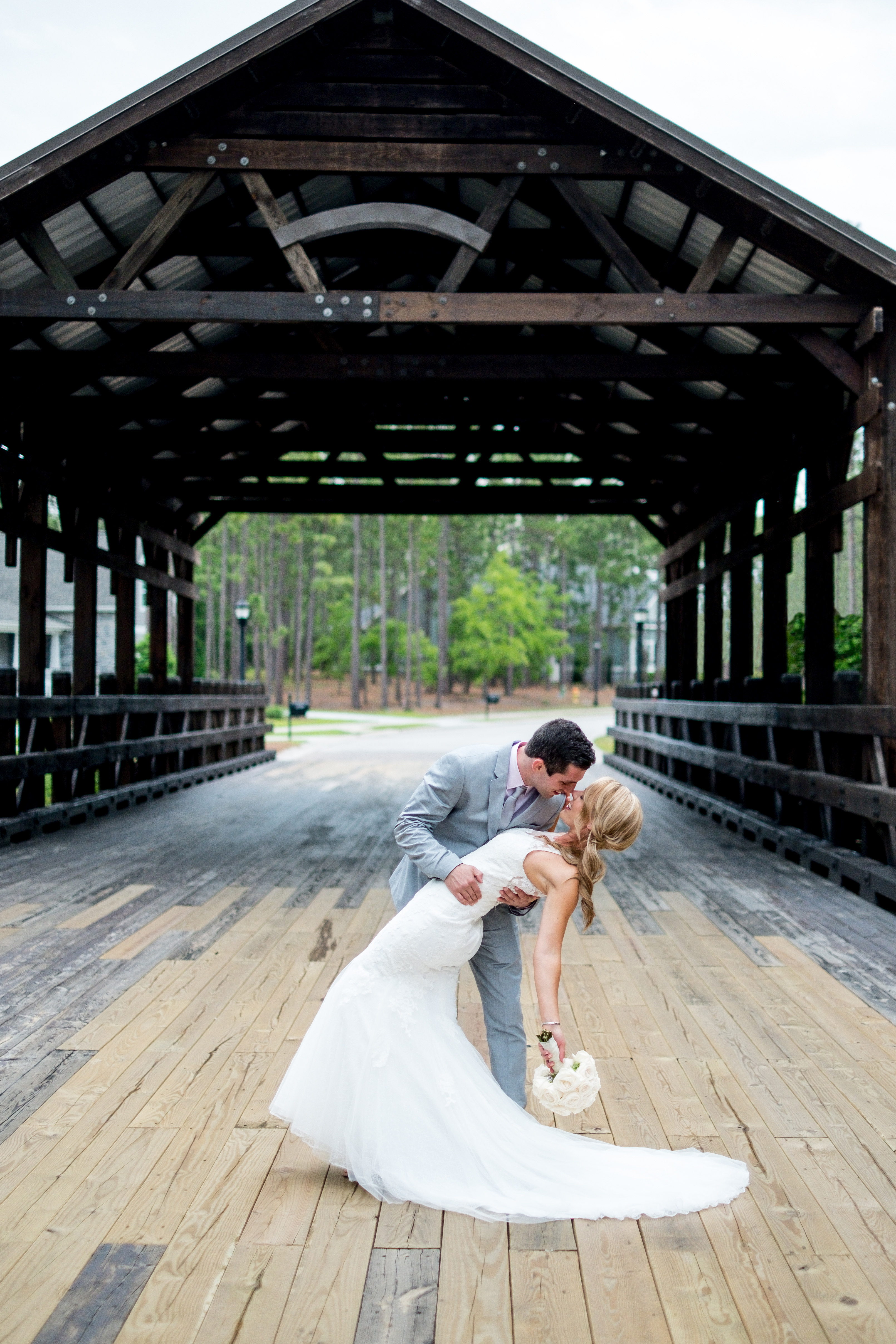 A groom dipping his bride, on a wooden bridge. Photo taken by Pait Photography, at a wedding at St. James Plantation, in St. James, NC.