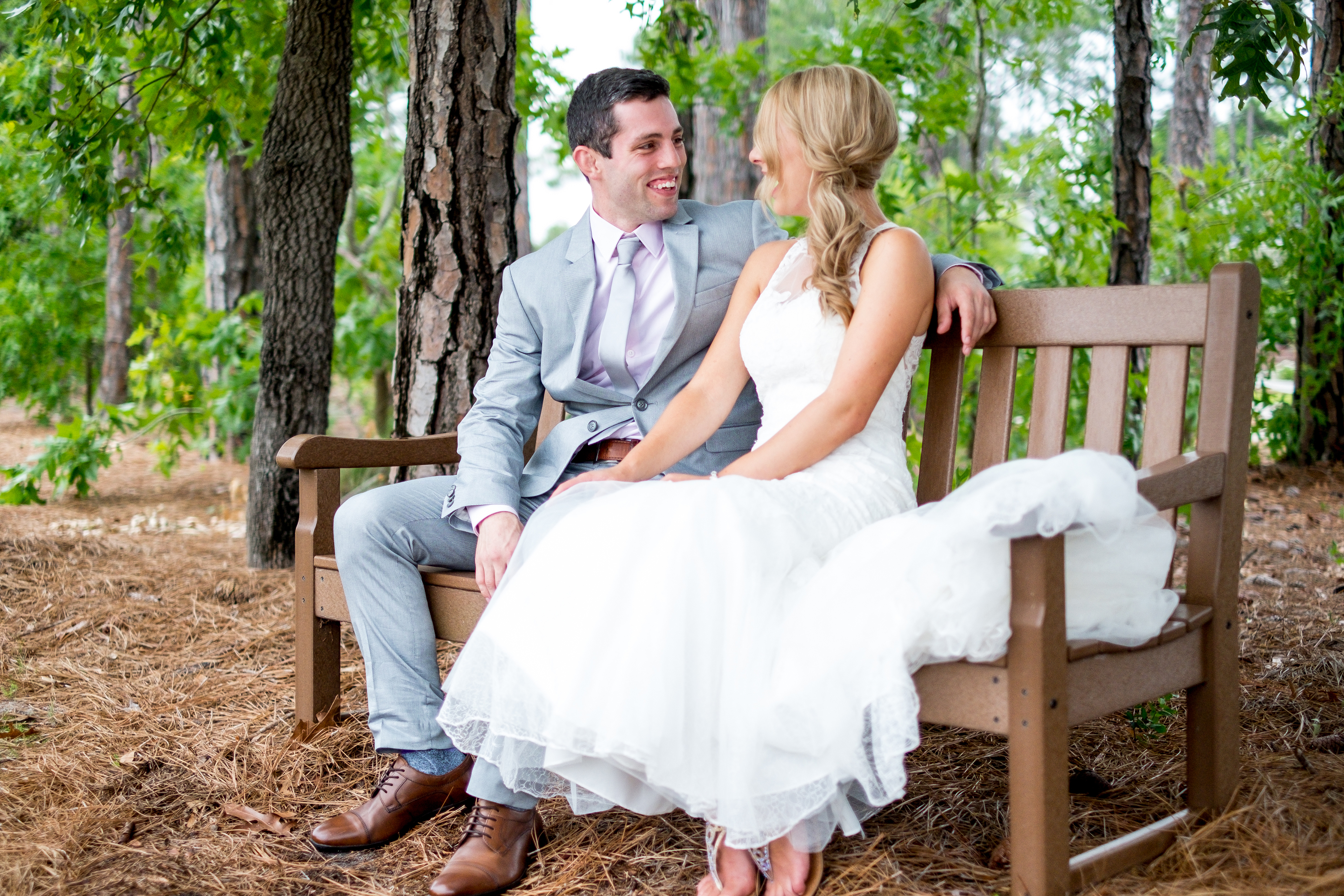 A bride and groom share a quiet moment on a bench, before their wedding. Photo taken by Pait Photography, at a wedding at St. James Plantation, in St. James, NC.