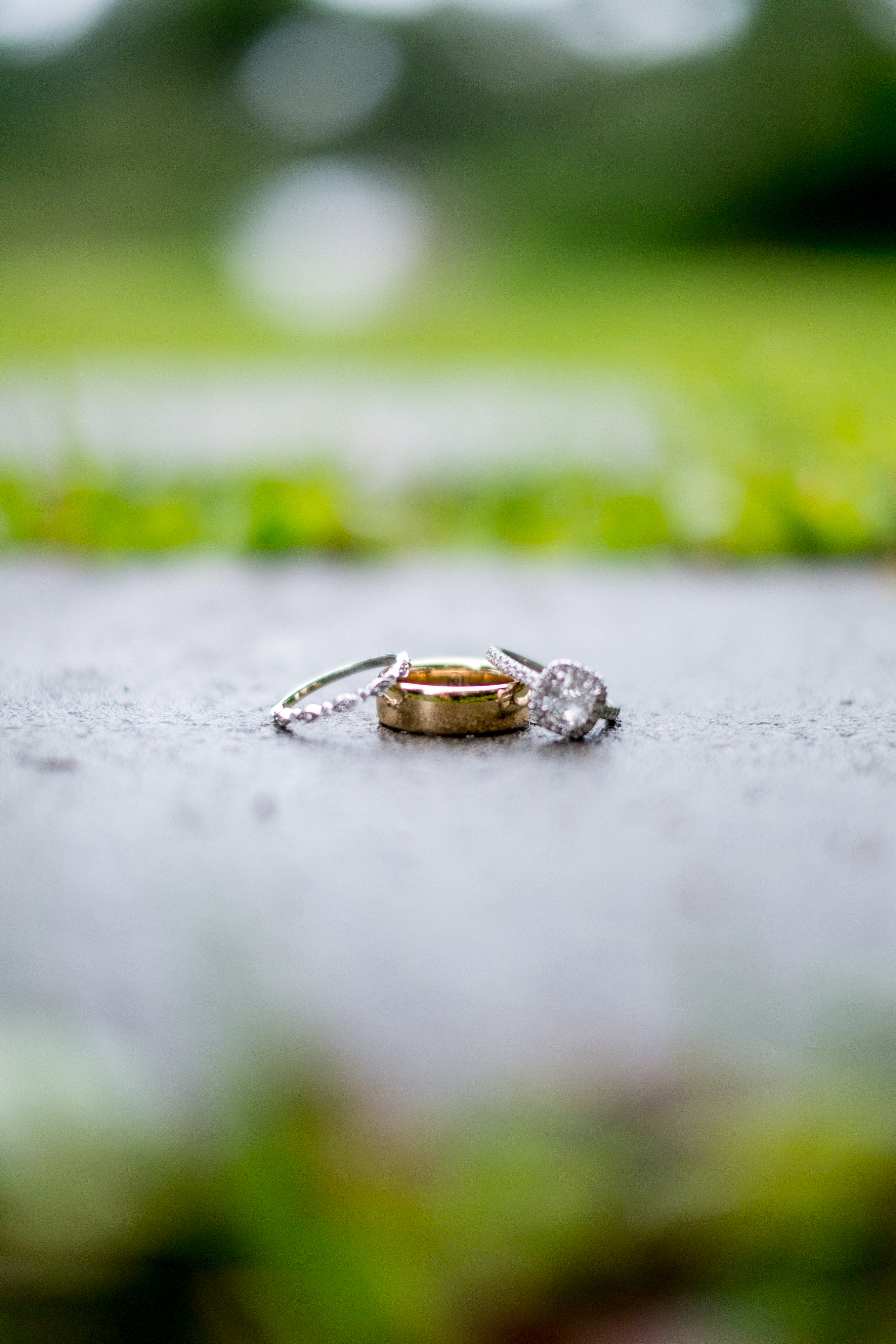 A close shot of the bride and grooms rings, sitting on a stone step, surrounded by the green of wet grass around the stone. Photo taken by Pait Photography, at a wedding at St. James Plantation, in St. James, NC.