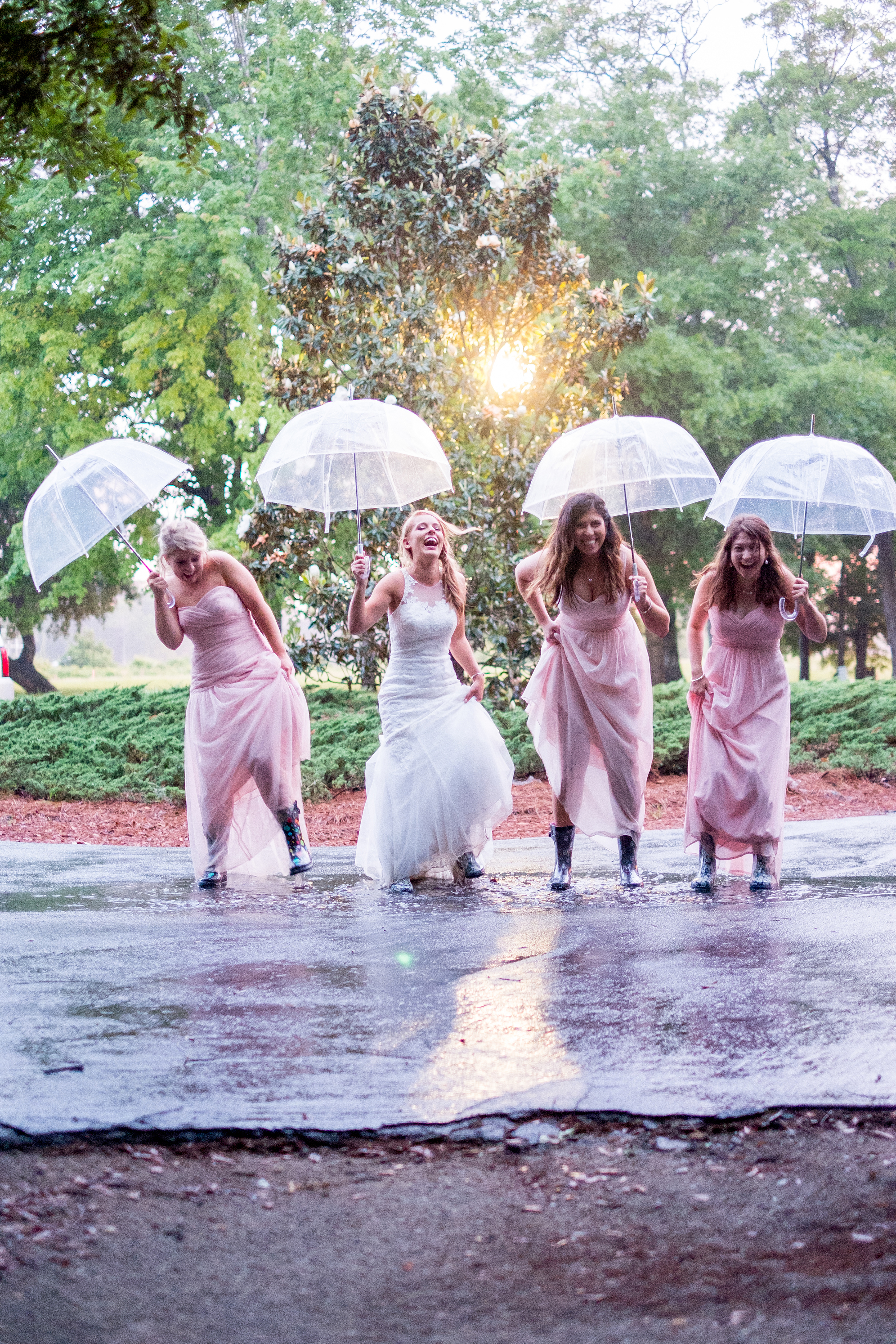 A bride and her bridesmaids, umbrellas in hand, and rain boots on their feet, sharing a laugh after jumping into a puddle. Photo taken by Pait Photography, at a wedding at St. James Plantation, in St. James, NC.