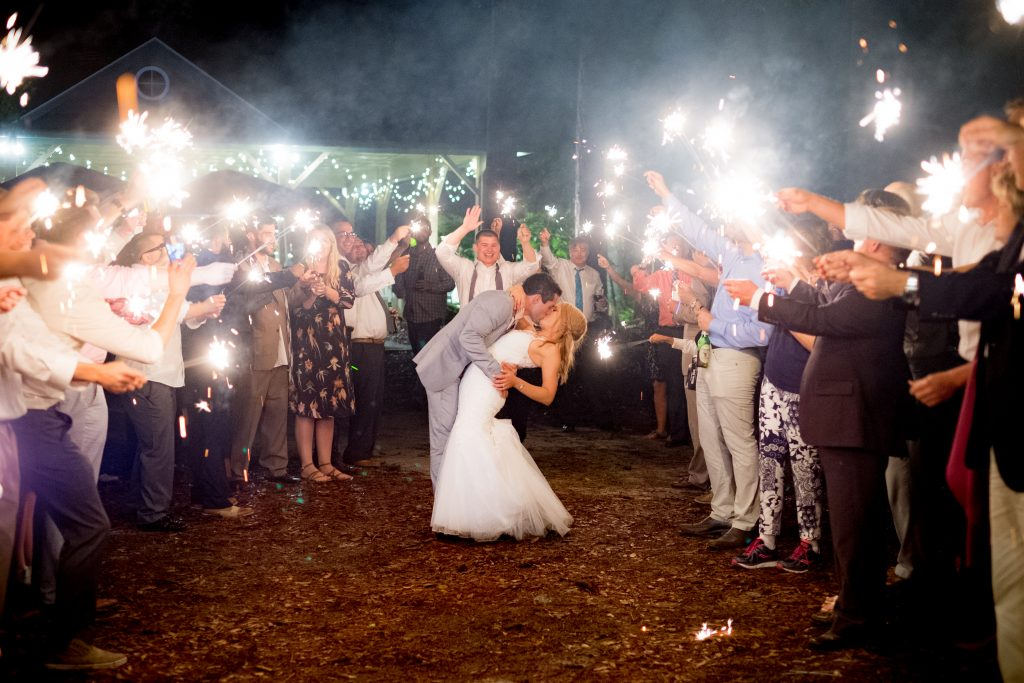A bride and groom kiss, as their guests hold sparklers around them, at the end of their wedding reception. Photo taken by Pait photography, at a wedding at St. James Plantation, in St. James, NC.