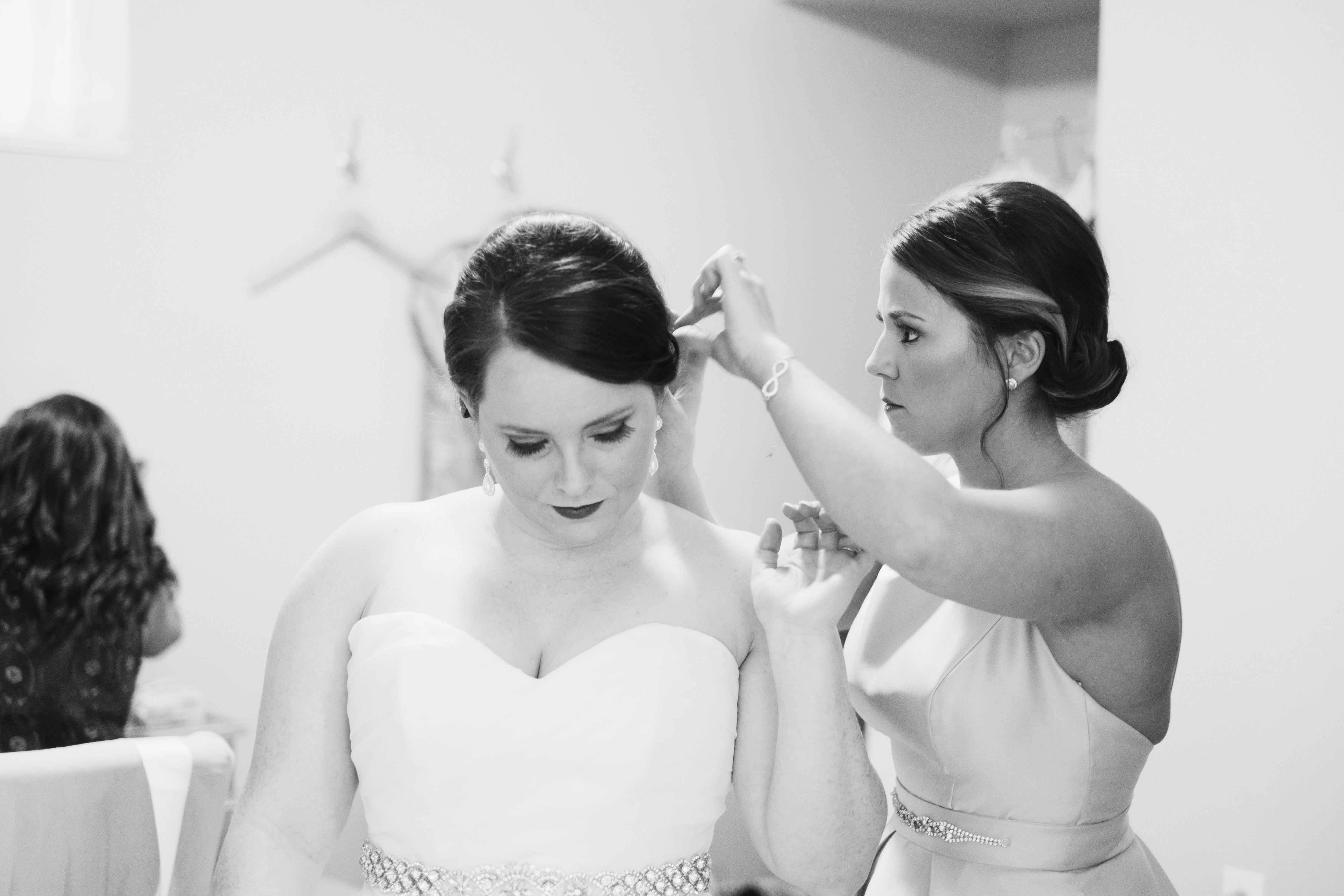 A photo of a bride and her maid of honor, making last-minute adjustments to the bride's hair, before her wedding. Photo taken by Pait Photography, at a wedding at St. Thomas Preservation Hall, in Wilmington, NC.