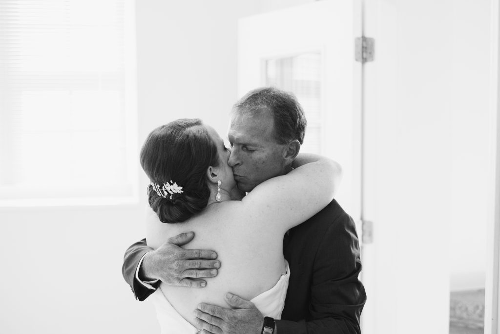 A black and white photo of a bride and her father, enjoying a last hug before her wedding. Photo taken by Pait Photography, at a wedding at St. Thomas Preservation Hall, in Wilmington, NC.