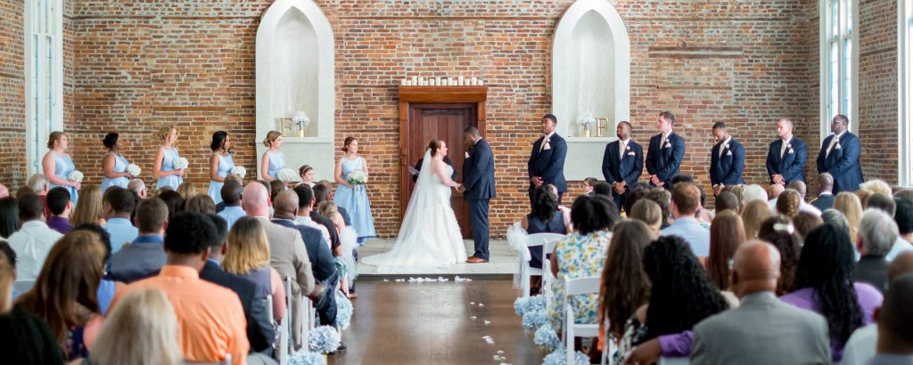 A photo of a wedding, taken from the back of the wedding hall. Photo taken by Pait Photography, at a wedding at St. Thomas Preservation Hall, in Wilmington, NC.