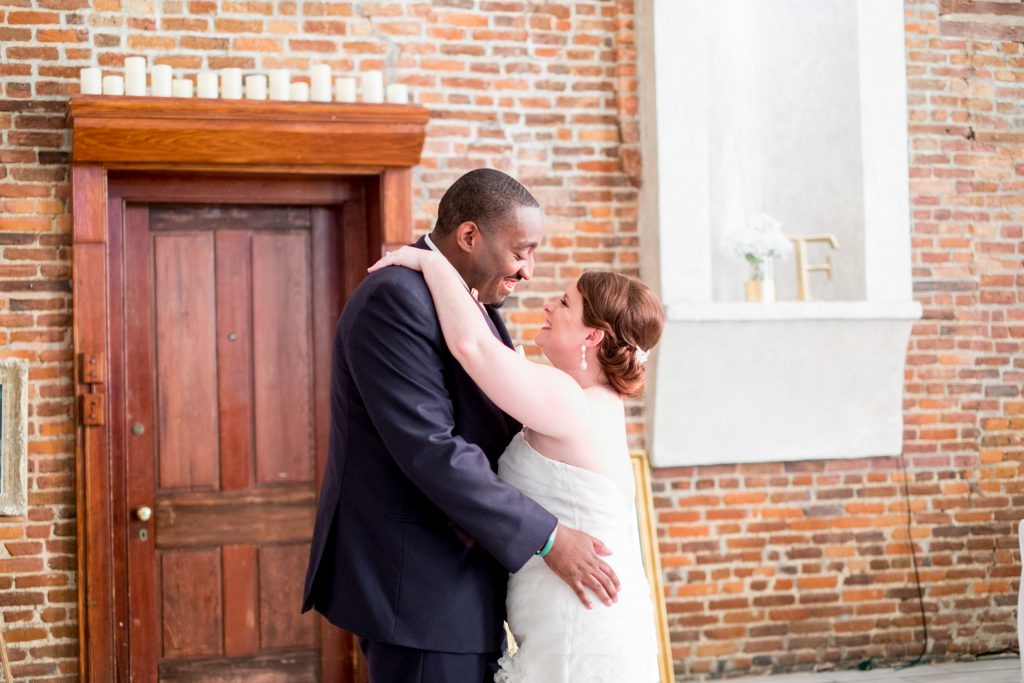 A photo of a bride and groom enjoying their first dance, during their wedding reception. Photo taken by Pait Photography, at a wedding at St. Thomas Preservation Hall, in Wilmington, NC.