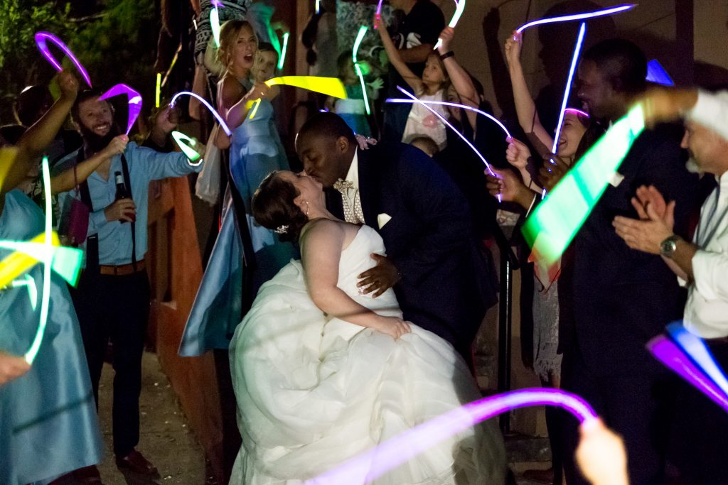 A photo of a bride and groom kissing under the glow of glowsticks being waved by their guests during the sendoff from their wedding reception. Photo taken by Pait Photography, at a wedding at St. Thomas Preservation Hall, in Wilmington, NC.