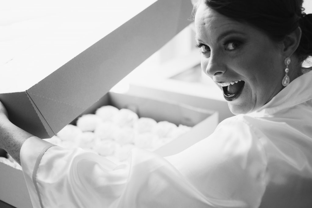 A black and white photo of a smiling bride opening the box containing her wedding cupcakes. Photo taken by Pait Photography, at a wedding at St. Thomas Preservation Hall, in Wilmington, NC.