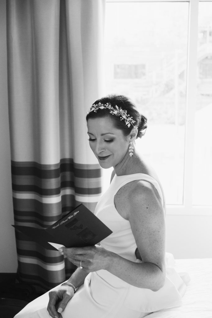 A black and white photo of a bride before her wedding, reading a card from her fiancé . Photo taken by Pait Photography, at a hotel, in Raleigh, NC.