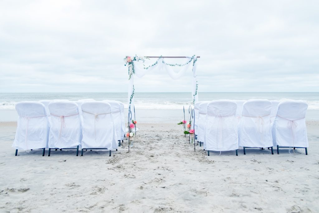 A photo of a wedding arbor and chairs for a wedding ceremony on the beach.