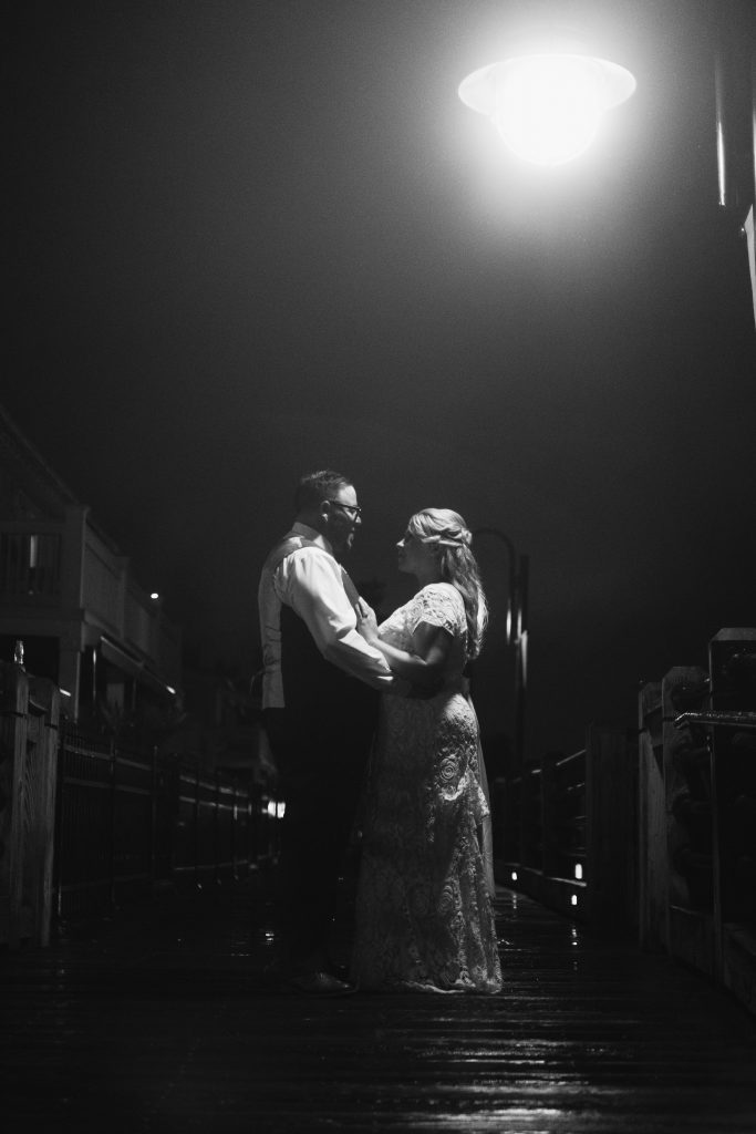 A black and white photo of a bride and groom embracing, at night, underneath a spotlight on the Wilmington Riverwalk.