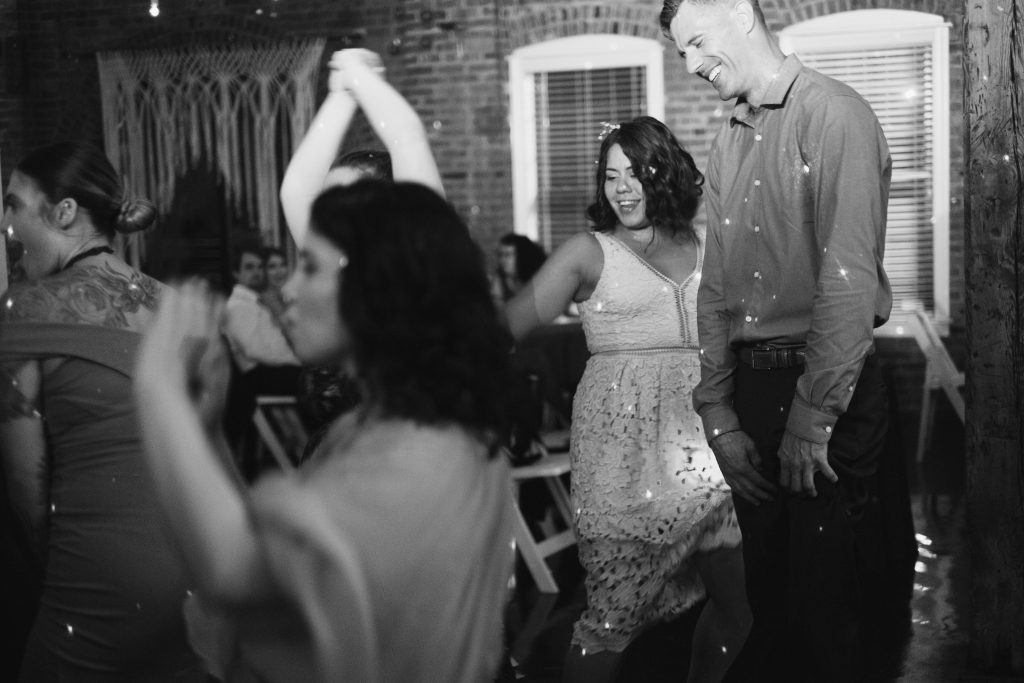 A black and white candid photo of guests dancing and laughing at a reception. Photo taken by Pait Photography, at a wedding at The River Room, in Wilmington, NC.