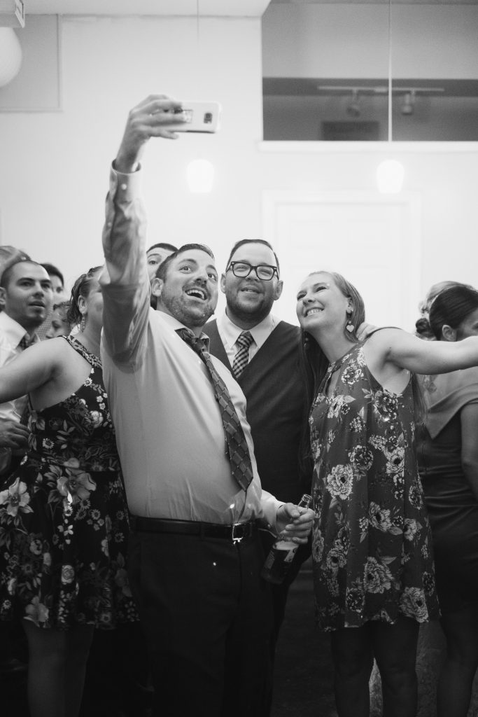 A black and white candid photo of guests and the groom taking a photo together with a phone.