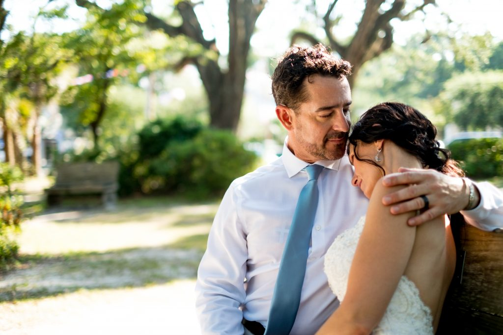 A photo of a groom and bride, embracing and sitting on a bench together, after their wedding ceremony. Photo taken by Pait Photography, at a wedding at Lois Jane's Riverview Inn, in Sounthport, NC.