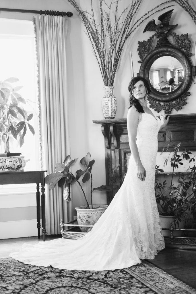 A black and white photo of a bride in her wedding dress, posed against a fireplace mantle inside of a historic inn. Photo taken by Pait Photography, at a wedding at Lois Jane's Riverview Inn, in Sounthport, NC.