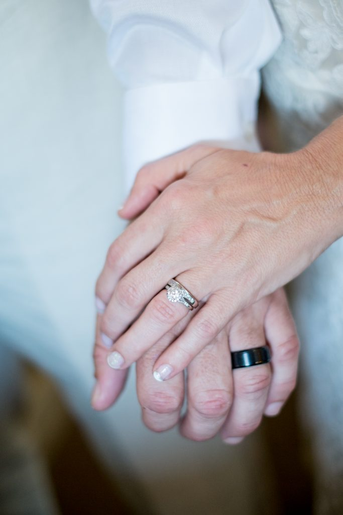 A detail photo of a bride and groom's hands, with a focus on their wedding rings. Photo taken by Pait Photography, at a wedding at Lois Jane's Riverview Inn, in Sounthport, NC.