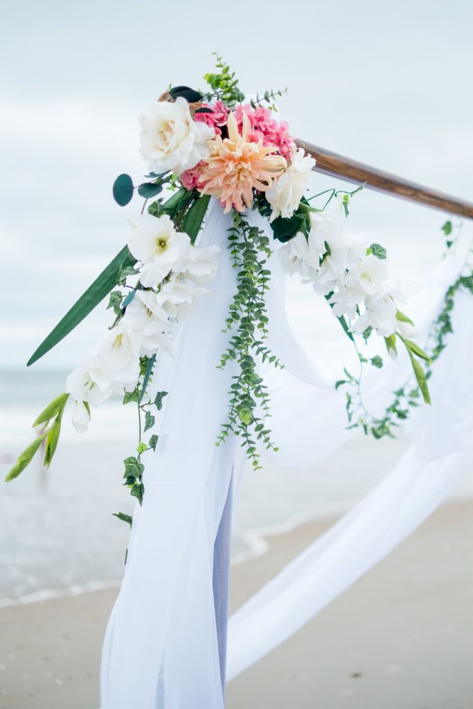 A detail photo of flowers on a wedding arbor,