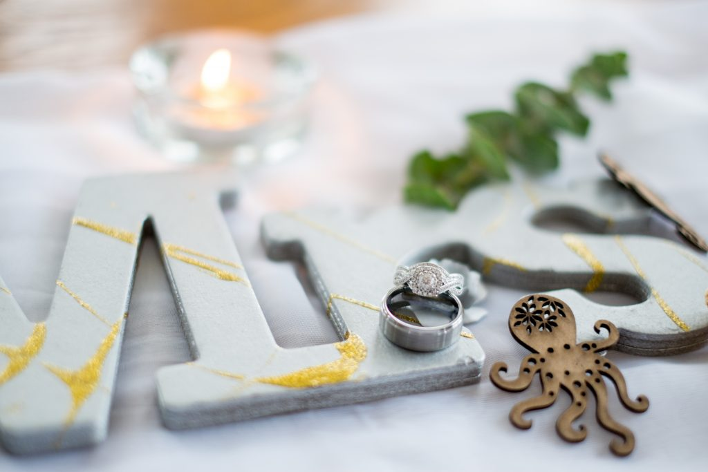 A detail photo of a bride and groom's wedding rings, surrounded by wedding decorations and a candle, on a table, inside of a beach house, Photo taken by Pait Photography, at a wedding on Topsail Island, NC.