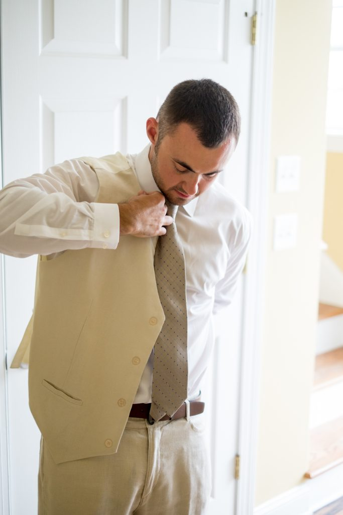 A photo of a groom putting on his vest before his wedding ceremony. Photo taken by Pait Photography, at a wedding on Topsail Island, NC.