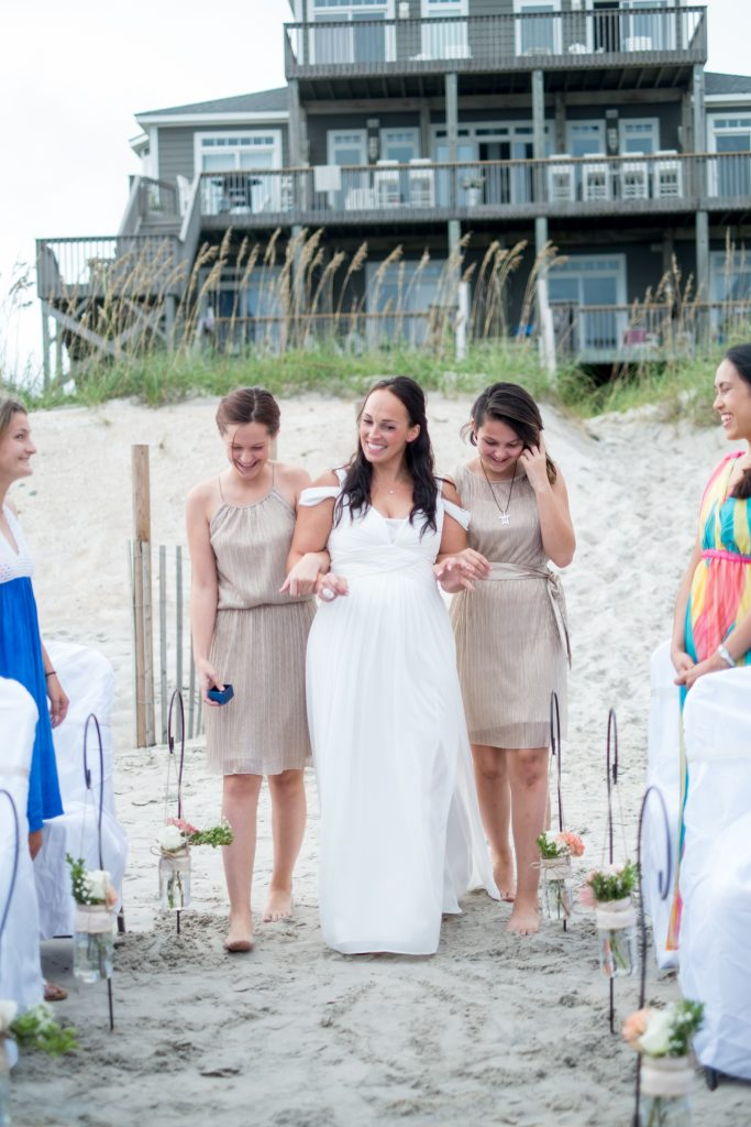 A photo of a bride and her daughters, walking her down the aisle during her wedding ceremony, on a beach, outside of a beach house, Photo taken by Pait Photography, at a wedding on Topsail Island, NC.