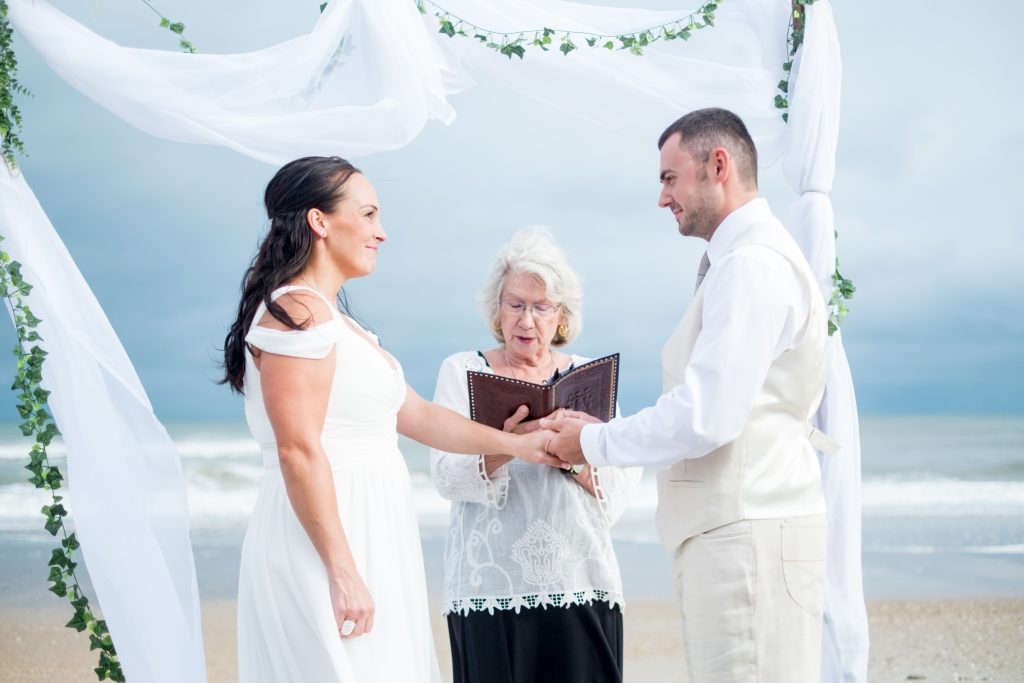 A photo of a bride and groom exchanging wedding rings during their wedding ceremony, Photo taken by Pait Photography, at a wedding on Topsail Island, NC.