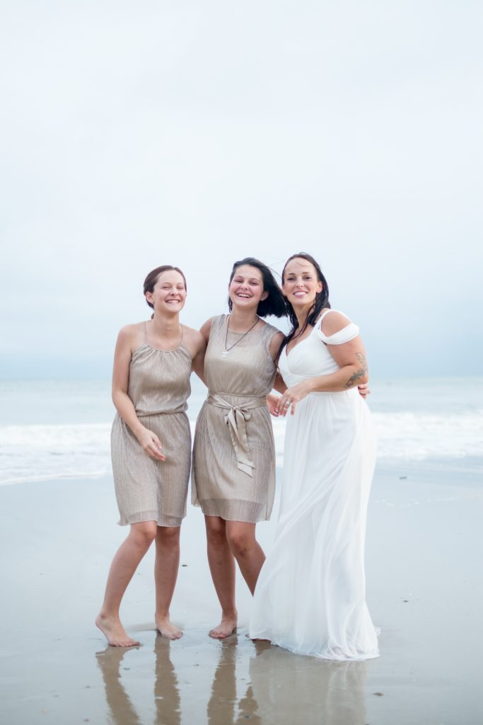 A photo of a bride and her daughters on the beach, after a wedding ceremony,