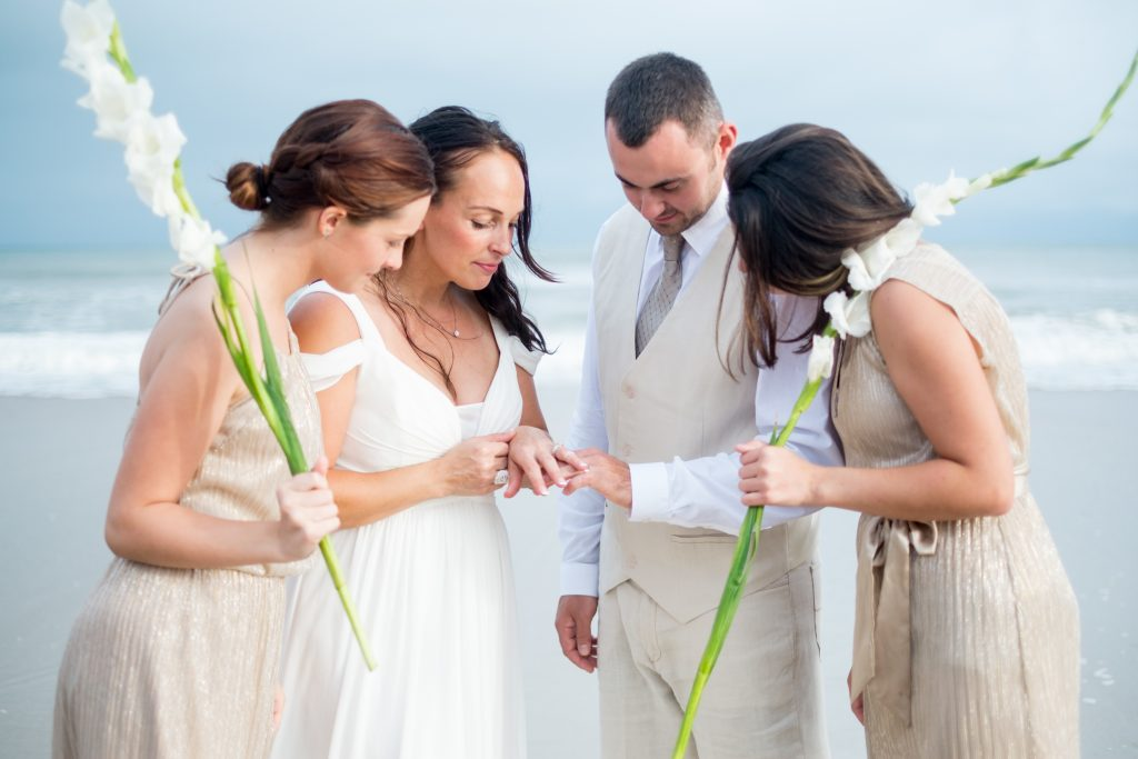 A photo of a bride, her daughters, and a groom admiring their wedding rings, on the beach, after the wedding ceremony. Photo taken by Pait Photography, at a wedding on Topsail Island, NC.