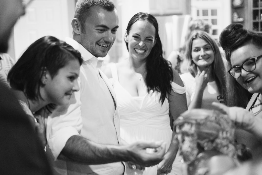 A black and white photo of a bride and groom, laughing while opening wedding presents, surrounded by their family, inside of a beach house,