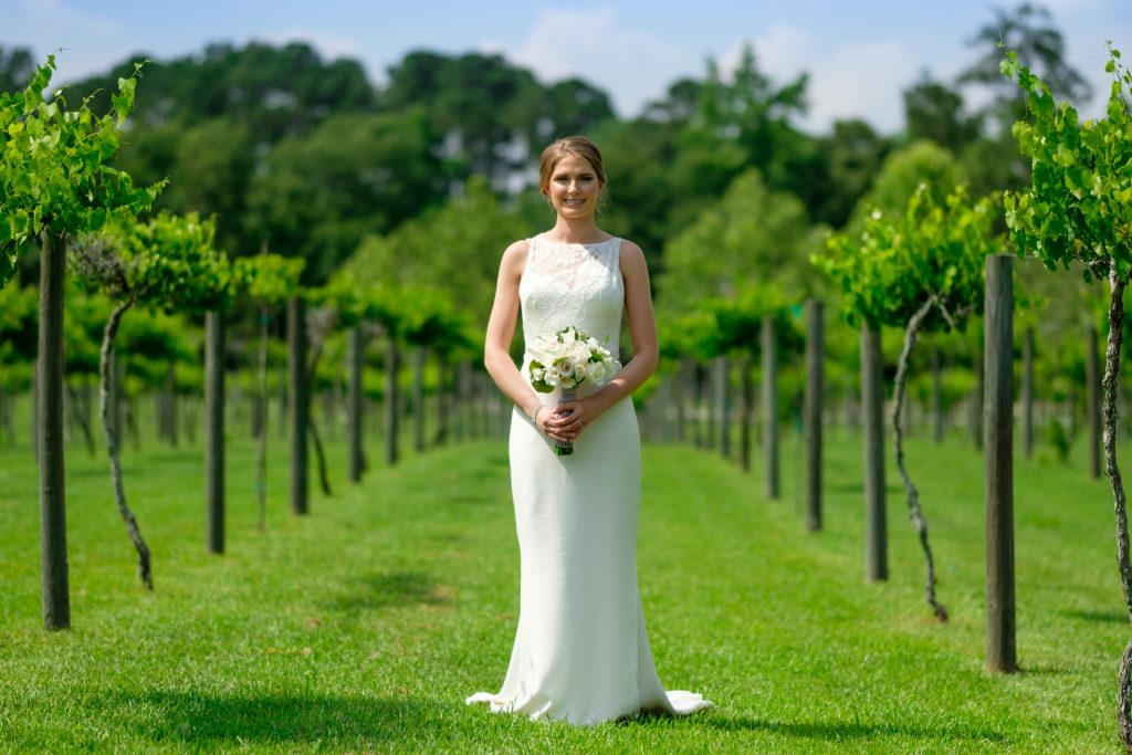 A photo of a bride posing with her wedding bouquet, in the middle of a vineyard. Photo taken by Pait Photography, at a wedding at the Cape Fear Winery and VIneyard, in Elizabethtown, NC.
