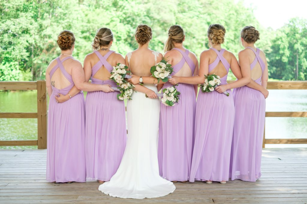 A photo of a the backs of a bride and her bridal party, embracing, and displaying their wedding bouquets. Photo taken by Pait Photography, at a wedding at the Cape Fear Winery and VIneyard, in Elizabethtown, NC.