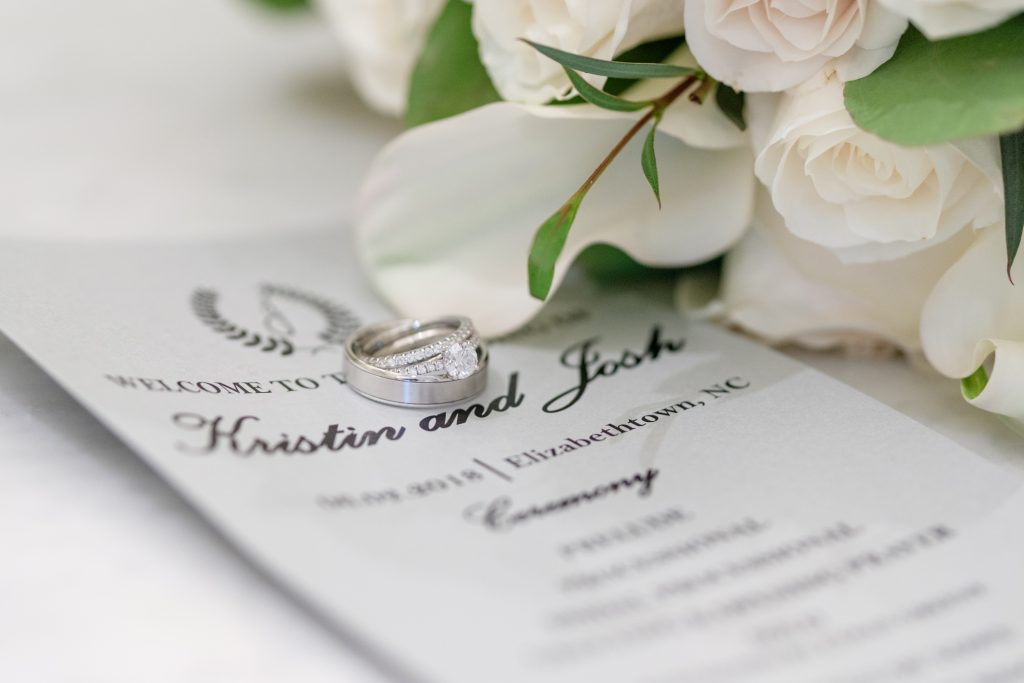 A detail photo of a set of wedding rings on a wedding invitation, in front of a wedding bouquet.