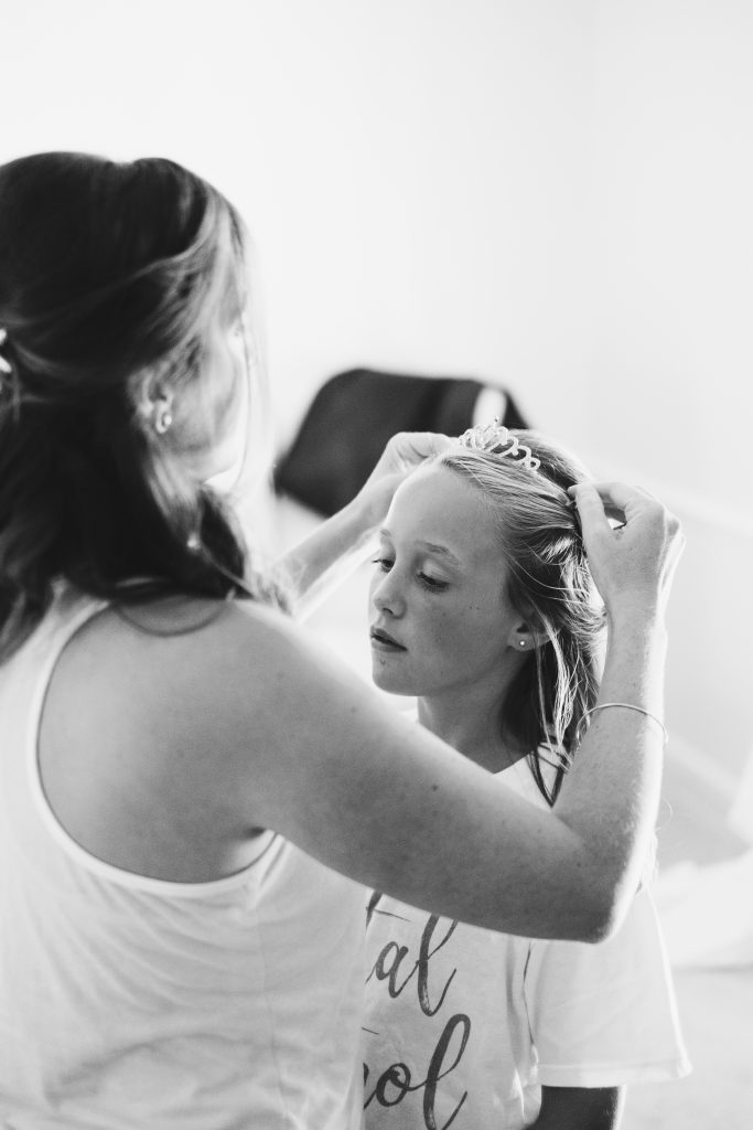 A black and white photo of a flower girl and her mom, who is putting a crown into her hair.