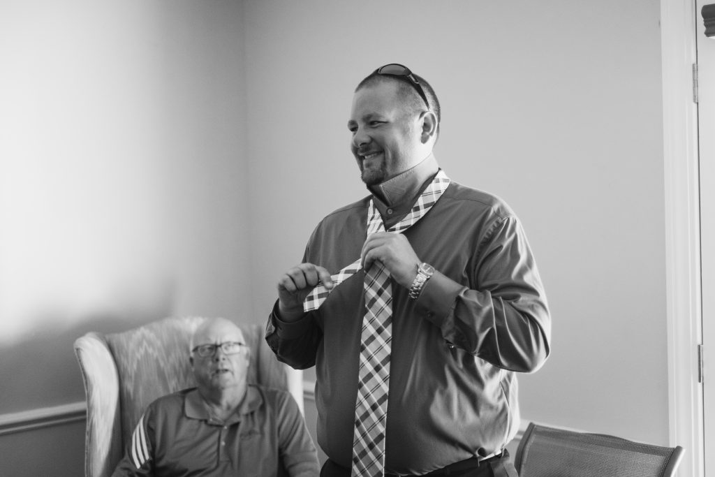 A black and white photo of a groom smiling and putting on his tie. Photo taken by Pait Photography, at a wedding at Beau Rivage Golf and Resort, in Wilmington, NC