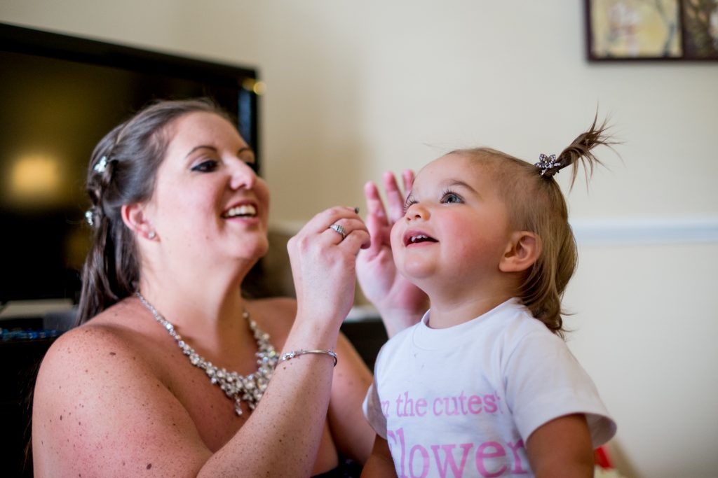 A photo of a bride at her wedding, sitting and laughing with her young daughter, while she does her hair.