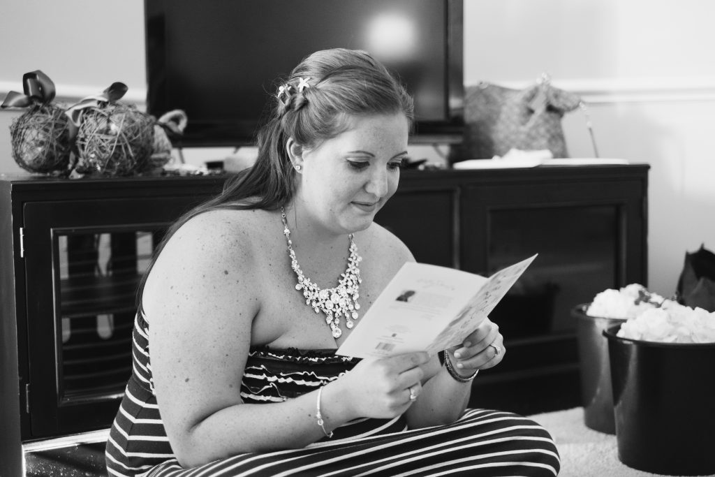 A black and white photo of a bride reading a card from her fiancé.